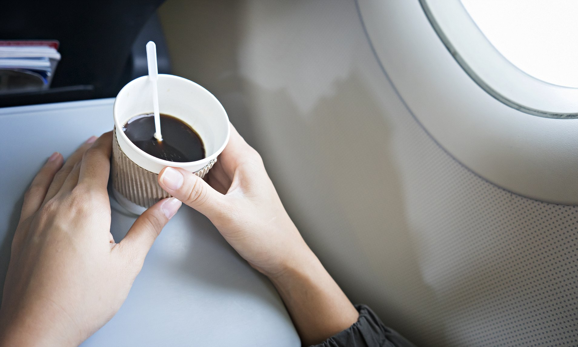 Woman drinking coffee on airplane.Woman hand holding white paper cup of hot coffee on the airplane. ; Shutterstock ID 726590566; Purchase Order: -