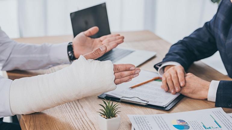 verkürzte Ansicht des Arbeitnehmers mit gebrochenen Arm Standortwahl am Tisch mit dokumentiert gegenüber Geschäftsmann in Büro, Entschädigung Konzept