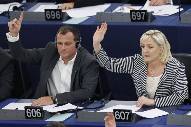 France's members of the European Parliament Marine Le Pen (R) and her companion Louis Aliot take part in a voting session at the European Parliament in Strasbourg, March 10, 2015.  REUTERS/Vincent Kessler