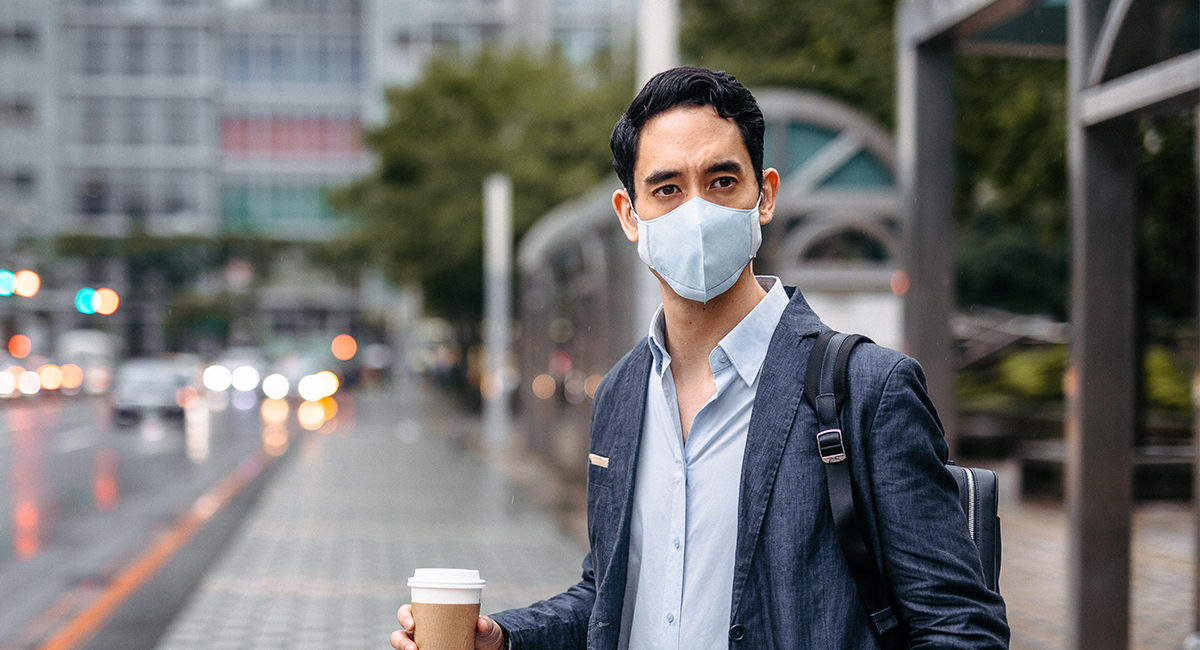 Businessman with takeaway coffee and flu mask on city street
